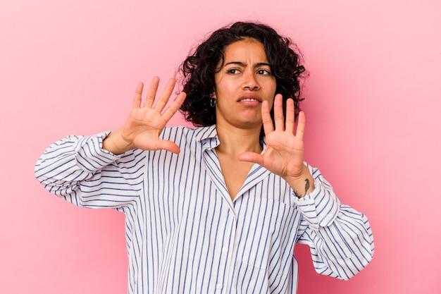 Молодая фигурная латинская женщина, изолированная на розовом фоне, отвергая кого-то, показывая жест отвращения.