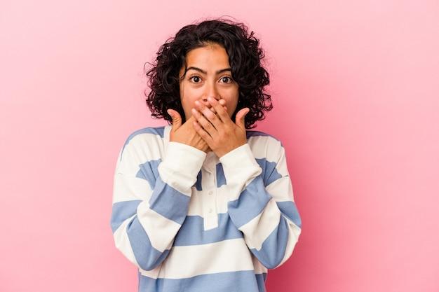 분홍색 배경에 고립된 젊은 곱슬머리 라틴 여성은 손으로 입을 가리고 충격을 받았습니다.