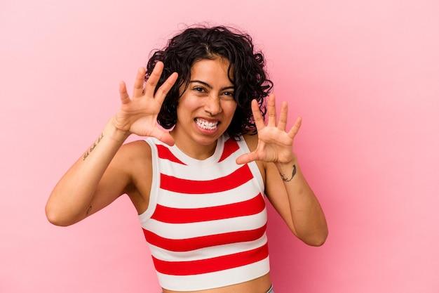 ピンクの背景に分離された若い巻き毛のラテン女性は、猫を模倣した爪、攻撃的なジェスチャーを示しています。