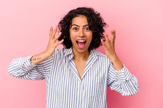 ピンクの背景に手で 10 番を示す若い巻き毛のラテン女性。