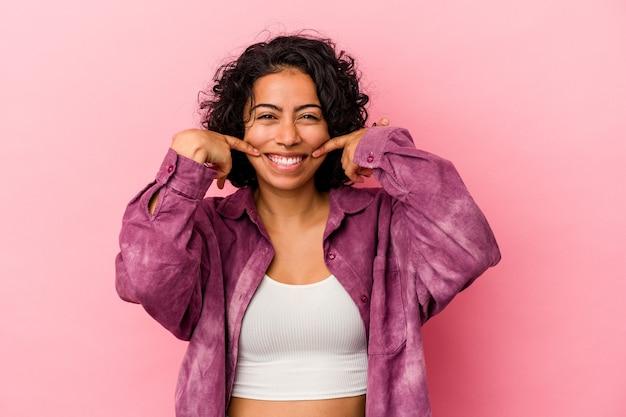 입에서 손가락을 가리키는 분홍색 배경 미소에 고립 된 젊은 곱슬 라틴 여자.