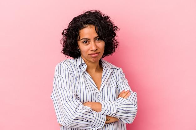 지루하고 피곤하고 긴장을 풀어야하는 분홍색 배경에 고립 된 젊은 곱슬 라틴 여자.