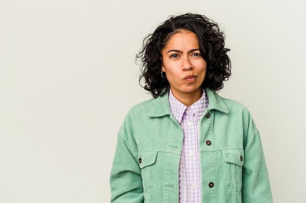 白い背景で隔離の若い巻き毛のラテン女性は混乱し、疑わしく、不安を感じます。