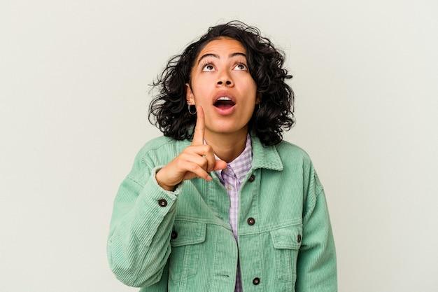 アイデア、インスピレーション コンセプトを持つ白い背景に分離された若い巻き毛のラテン女性。