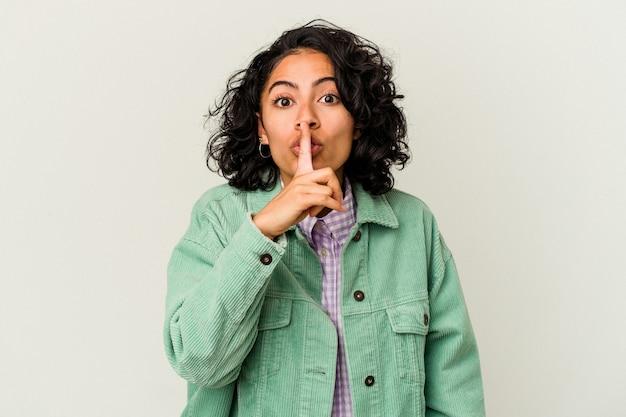 비밀을 유지하거나 침묵을 요구하는 흰색 배경에 고립 된 젊은 곱슬 라틴 여자.