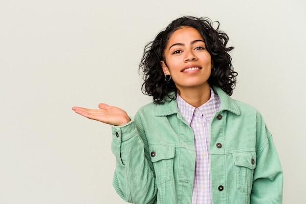 手のひらにコピー スペースを表示し、腰に別の手を保持している白い背景に分離された若い巻き毛のラテン女性。