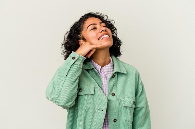 指で携帯電話の呼び出しジェスチャーを示す白い背景で隔離の若い巻き毛のラテン女性。