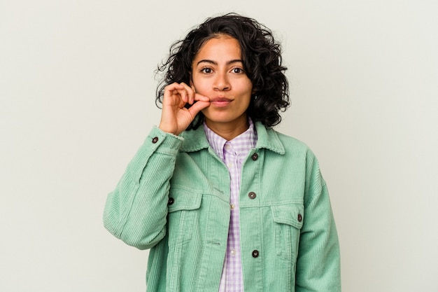 秘密を守る唇に指で白い背景に分離された若い巻き毛のラテン女性。