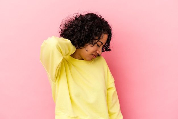 Young curly latin woman isolated on pink background having a neck pain due to stress, massaging and touching it with hand.