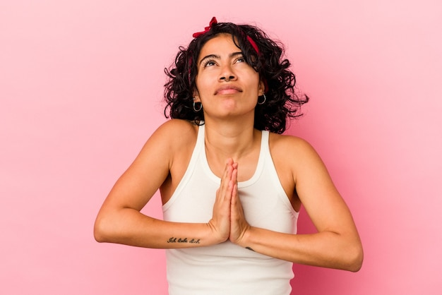 Young curly latin woman isolated on pink background holding hands in pray near mouth, feels confident.