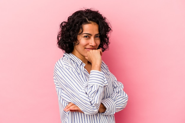 Young curly latin woman isolated on pink background suspicious, uncertain, examining you.