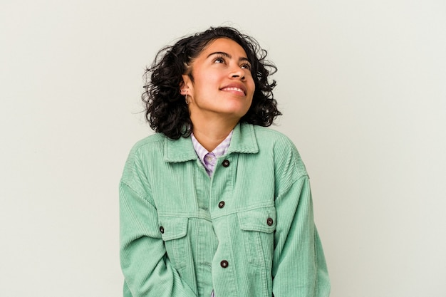 Young curly latin woman isolated on white background dreaming of achieving goals and purposes