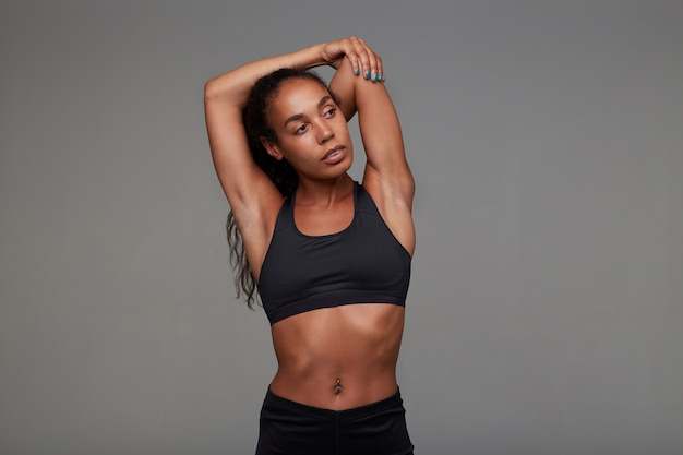Young curly long haired brunette lady with dark skin being in good physical shape, goes in for sport every day, dressed in sporty wear while posing