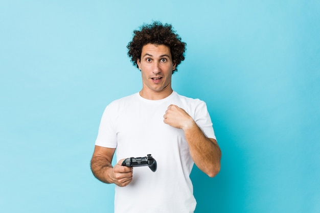 Молодой кудрявый мужчина держит игровой контроллер с удивлением, указывая на себя и широко улыбаясь