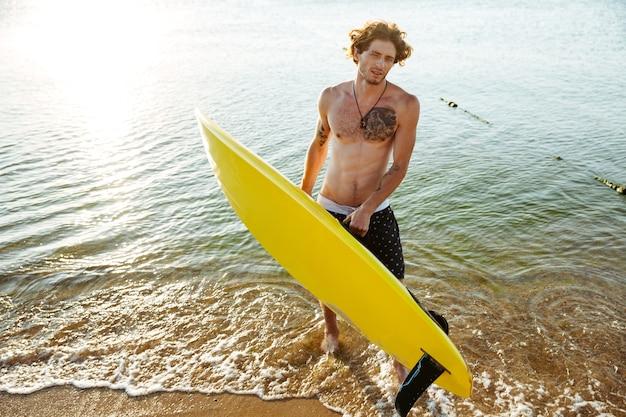 해변에서 바다에 서있는 동안 그의 서핑 보드를 들고 곱슬 젊은이