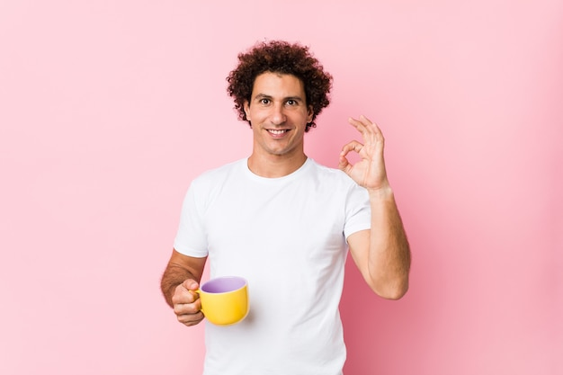 Young curly man holding a tea cup cheerful and confident showing ok gesture