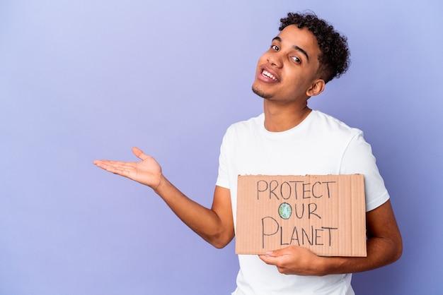 手のひらにコピースペースを示し、腰に別の手を持って私たちの惑星を保護するを保持して孤立した若い巻き毛の男