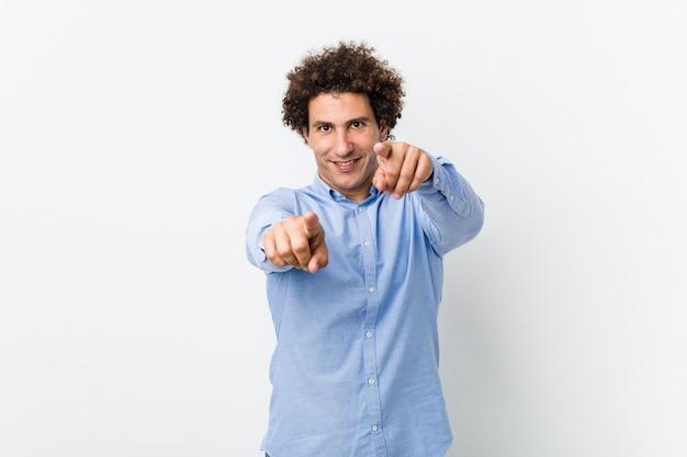 エレガントなシャツを着た若い中年成熟した男は前を指している陽気な笑顔を笑っています。