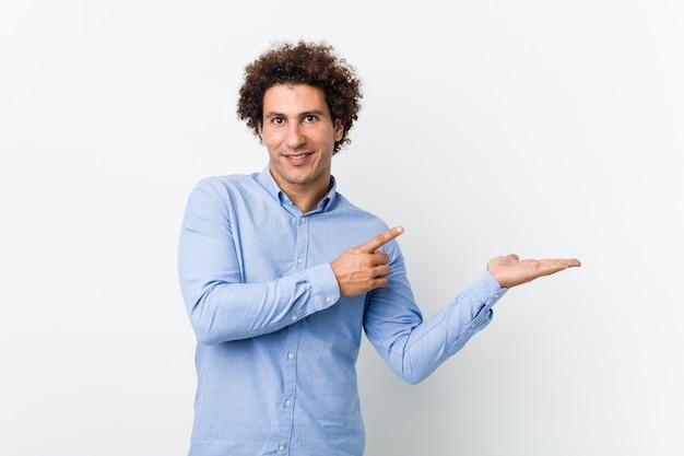 エレガントなシャツを着ている若い巻き毛の成熟した男は手のひらにコピースペースを持って興奮しています。