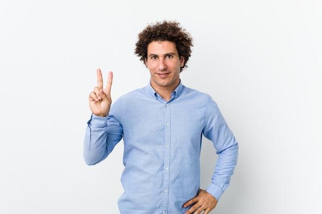 指で番号2を示すエレガントなシャツを着ている若い中年の男。