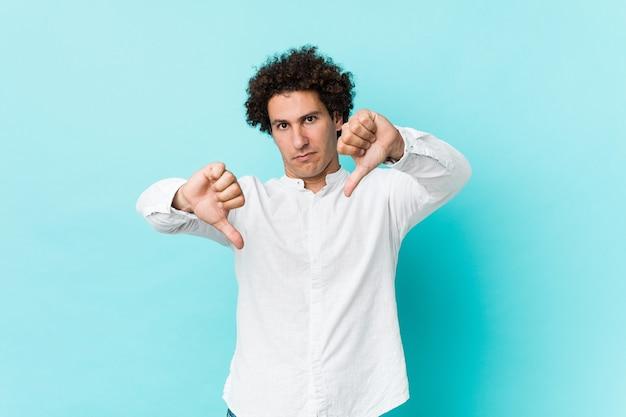아래로 엄지 손가락을 표시하고 싫어하는 표현 우아한 셔츠를 입고 젊은 곱슬 성숙한 남자.