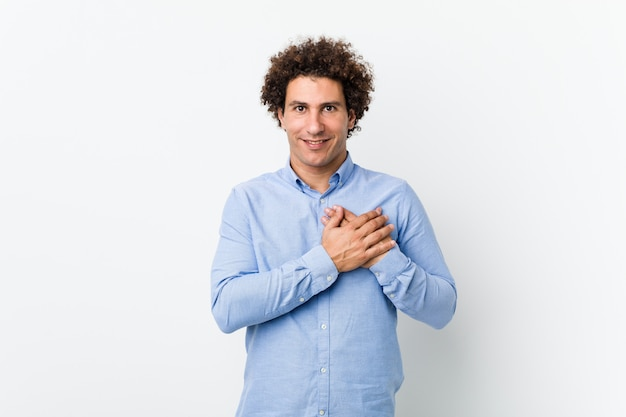 Young curly mature man wearing an elegant shirt has friendly expression, pressing palm to chest.