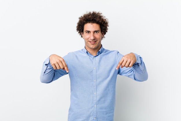 Young curly mature man wearing an elegant shirt points down with fingers, positive feeling.