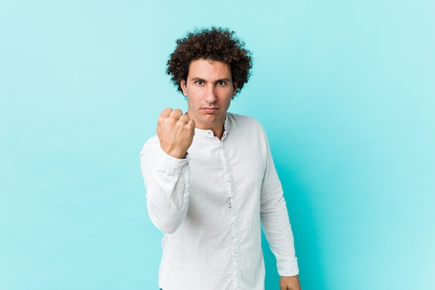 Young curly mature man wearing an elegant shirt showing fist to camera, aggressive facial expression.