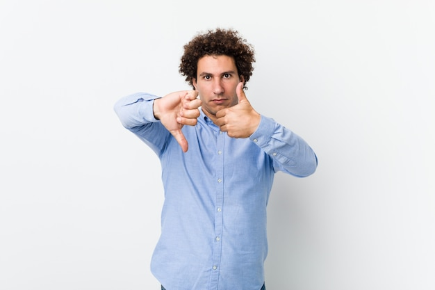 Young curly mature man wearing an elegant shirt showing thumbs up and thumbs down