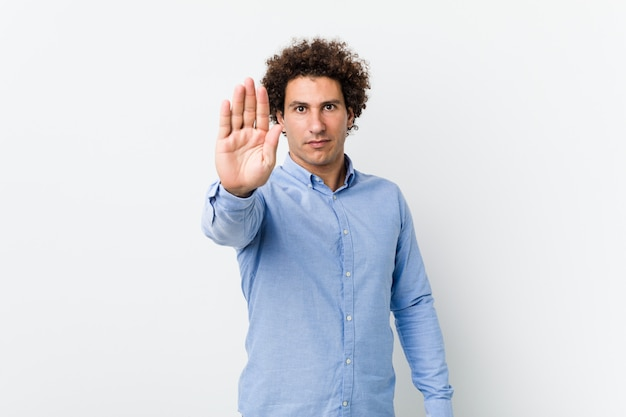Young curly mature man wearing an elegant shirt standing with outstretched hand showing stop sign, preventing you.