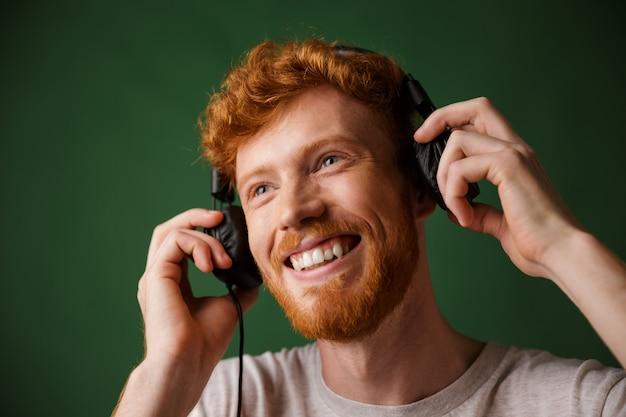 Young curly readhead bearded man is enjoying listening to music
