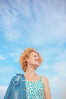 Young curly redhead woman in straw hat blue sundress and jeans jacket standing on blue sky