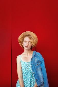 Young curly redhead woman in straw hat blue sundress and jeans jacket standing on dark red backgrou