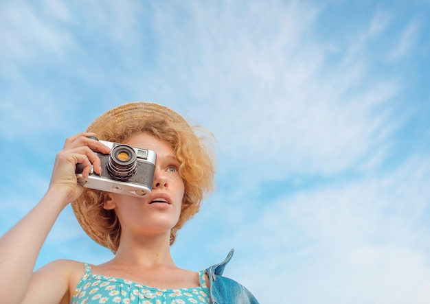 Young curly redhead woman in straw hat blue sundress and jeans jacket standing with vintage camera