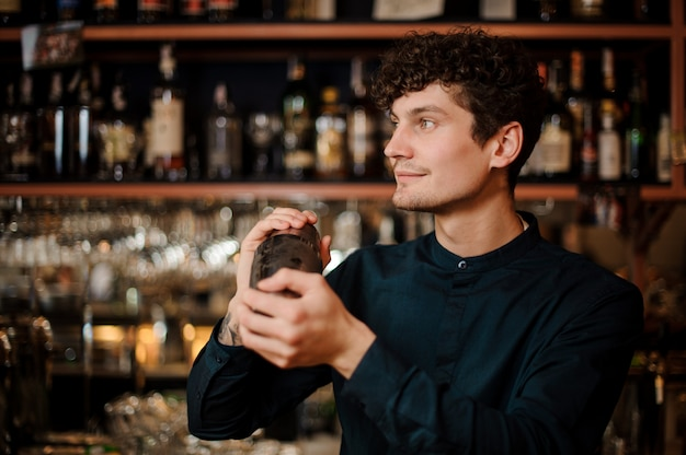 Young curly smiling barman shaking alcoholic drink