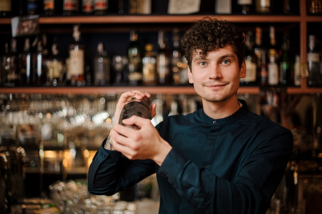 Young curly smiling bartender shaking alcoholic drink