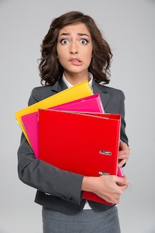 Young curly stressed shocked business woman biting bottom lip holding colorful folders