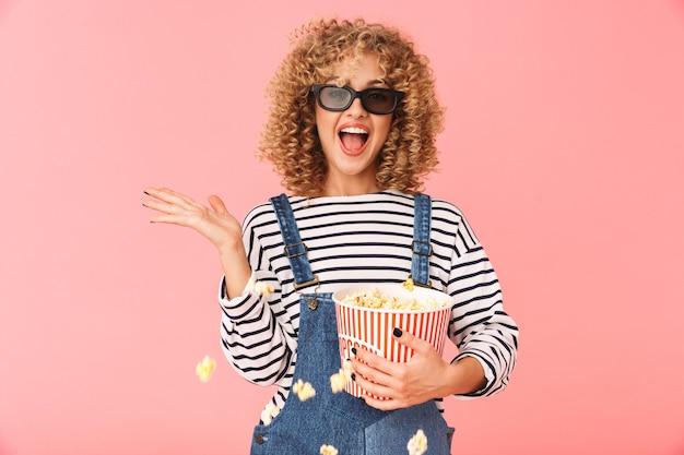 Молодая кудрявая женщина 20 лет держит ведро попкорна стоя