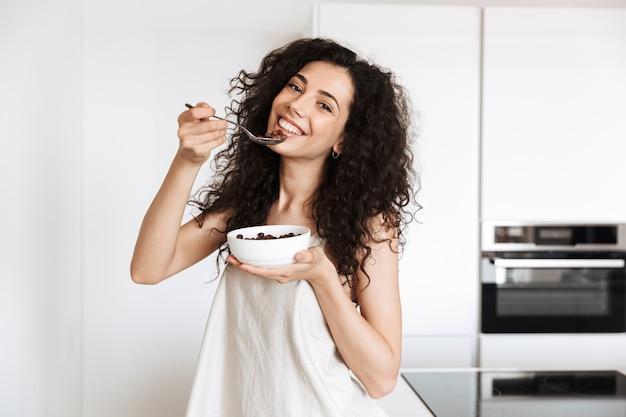 Молодая кудрявая женщина 20 лет в шелковой одежде для отдыха завтракает на кухне и ест шоколадную мюсли с молоком