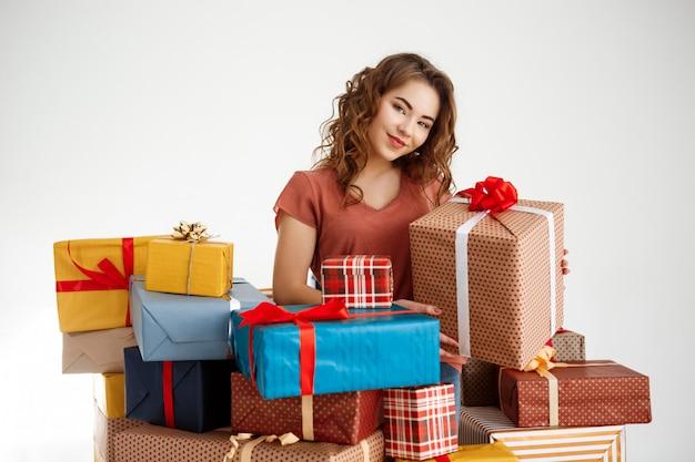 Молодая кудрявая женщина среди подарочных коробок на белом