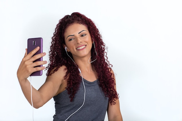 Young curly woman in casual clothes taking a selfie