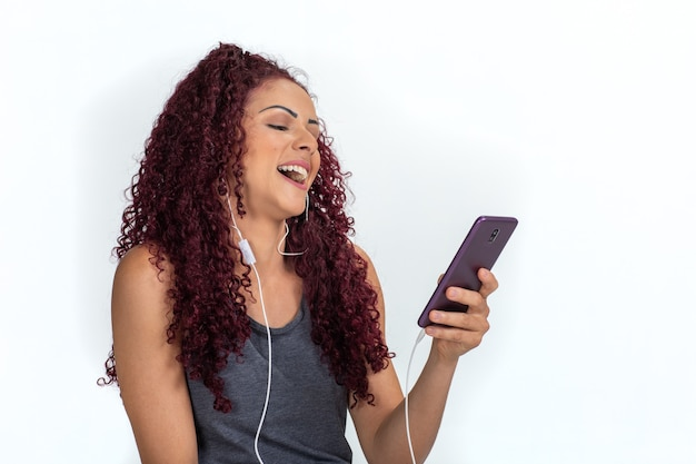 Young curly woman in casual clothes with earphones