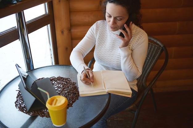 Молодая кудрявая женщина сосредоточилась на работе, пишет в дневнике, разговаривает со смартфоном, сидя у окна в творческом деревянном кафе