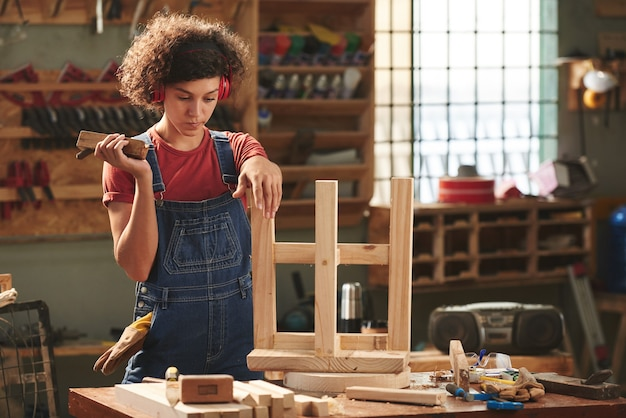 Young curly woman in ear defenders and denim overall holding hand plane and looking at finished wooden stool pensively before polishing it