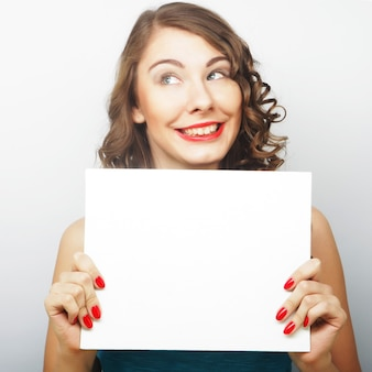 Young curly woman holding blank card
