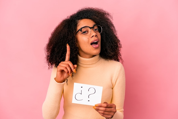 Young curly woman holding an interrogation on a placard having an idea, inspiration concept