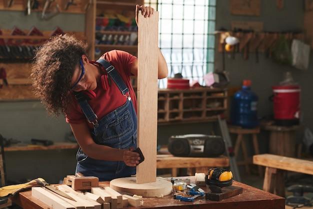 Молодая кудрявая женщина в джинсовом комбинезоне и защитных очках наслаждается процессом полировки деревянной доски наждачной бумагой