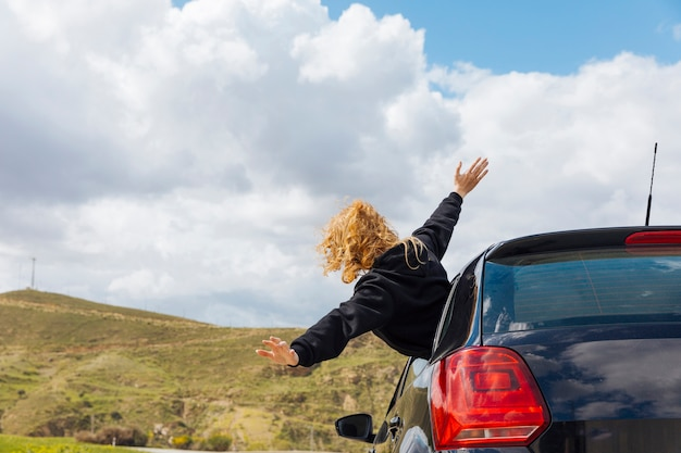 Young curly woman leaning out of car window