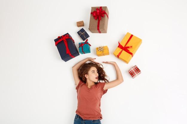 선물 상자 가운데 누워 젊은 곱슬 여자