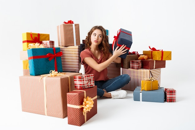 Young curly woman sitting on floor among gift boxes guessing what is inside